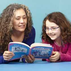 Girl reading book with Therapist.