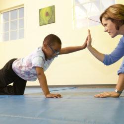 Boy doing exercises on floor.