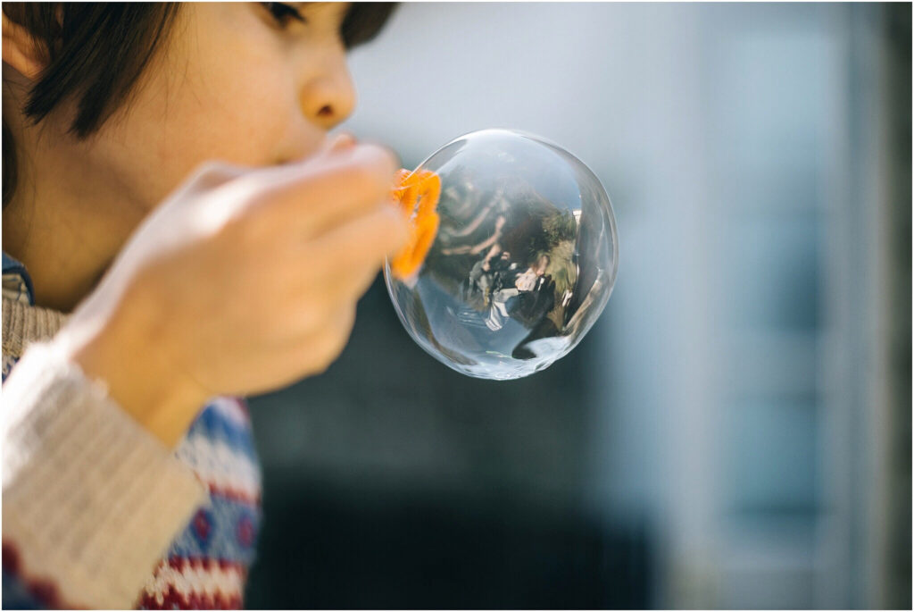 Image of child bowing bubbles